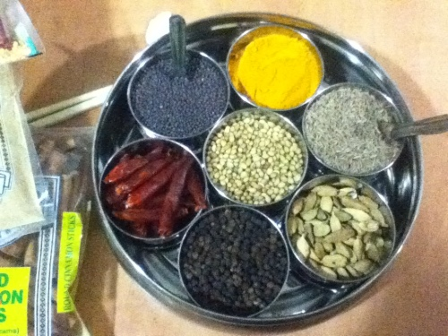 Clockwise starting with the yellow stuff: turmeric, cumin seed, green cardamom, black peppercorn, dried red chilies, black mustard seed; center is coriander seed.