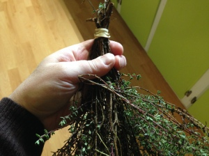 Once your herbs are dirt and caterpillar free shake off the excess water and blot with towels. Once dry, make little bundles of herbs. I like to use rubber bands for this because they will stay tight if the stems shrink as they dry. If you want, you can hang your bundles as is. However, exposure to light will fade the color and the flavor of your herbs. But there is a way to avoid that...